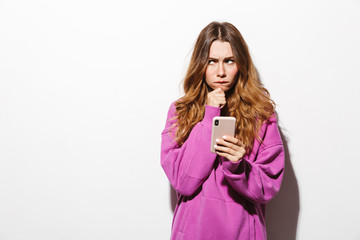 Portrait of resentful woman 20s wearing sweatshirt holding mobile phone while standing, isolated over white background