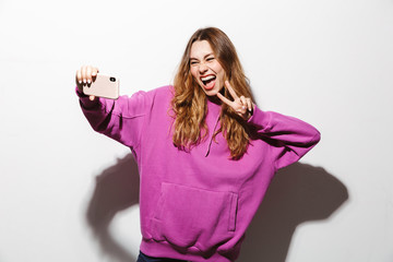 Portrait of attractive woman 20s wearing sweatshirt using smartphone and taking selfie photo, isolated over white background