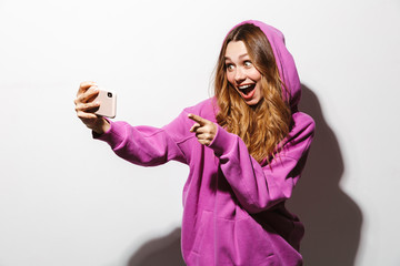 Portrait of beautiful woman 20s wearing sweatshirt using smartphone and taking selfie photo, isolated over white background