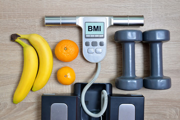 Body Mass Index Scale with fruits and dumbbells on wooden board.Healthy lifestyle concept.