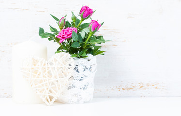 Decorative heart, pink roses and candles on white wooden backgro