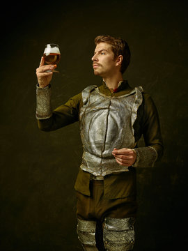 Medieval knight with beer on dark studio background. Portrait in low key of brutal man in tradishional retro costume of spanish hidalgo. Human emotions, comparison of eras and facial expressions
