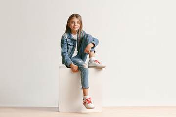 Full length portrait of cute little teen girl in stylish jeans clothes looking at camera and smiling against white studio wall. Kids fashion concept