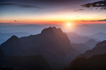 Mountaineer man standing on peak mountain range at sunset