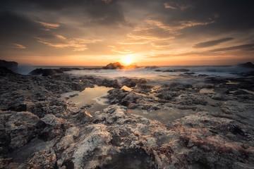 Sunrise on a rocky beach / Magnificent sea sunrise at the rocky Black sea coast