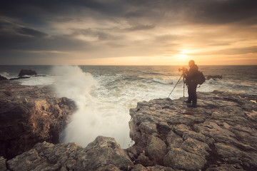 Sunrise on a rocky beach / Silhouette of a photographer taking photos of the sunrise