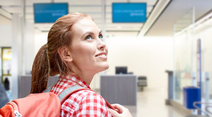 travel, tourism and people concept - smiling young woman with backpack over airport terminal background