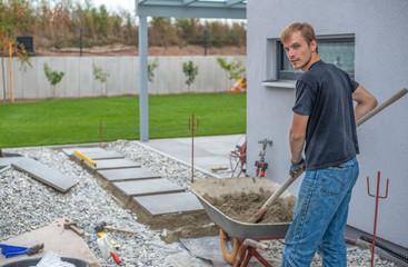 Junger Mann verlegt Trittplatten in Kiesfläche