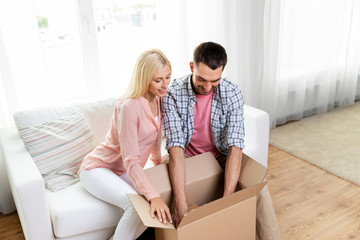 delivery, mail and people concept - happy couple with open parcel box at home