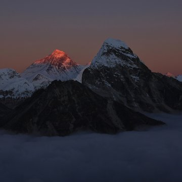 Last sunlight of the day illuminating the peak of Mount Everest. Sea of fog. View from a secret place in the Gokyo Valley, Nepal.