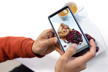 close up of young man using smart phone taking photo which take a picture food or bakery before eating, photography on white background