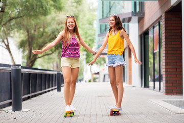 friendship, leisure and people concept - happy teenage girls or friends riding skateboards and holding hands on city street in summer