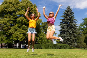 leisure, people and friendship concept - happy teenage girls or friends jumping and having fun at summer park