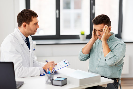 medicine, healthcare and people concept - doctor with clipboard and male patient suffering from sick headache at medical office in hospital