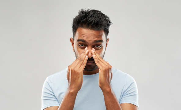 health problem and people concept - indian man rubbing nose over grey background