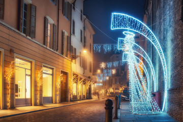 Night street decorated with light angels in Parma, Emilia-Romagna, Italy. Old architecture and landmark in Parma