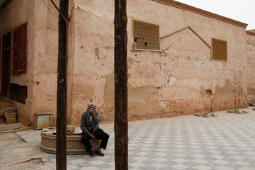 An elderly man holds his hand to his face in the Old City in Kashgar