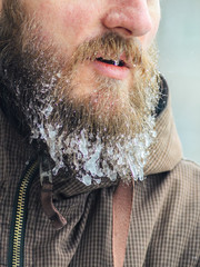 Part of the face of a serious and worried man is an icy beard with hanging icicles. Frosty harsh winter concept