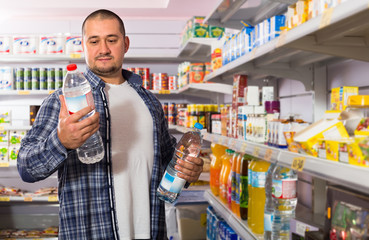 man choosing mineral water in grocery.