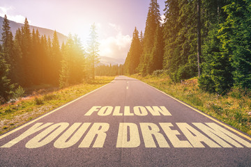 Follow your dream text written on road in the mountains