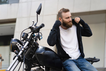 Smiling young biker with motorcycle putting on hoodie. Portrait of Caucasian bearded man sitting on motorbike outdoors. Biker culture concept