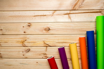 Colorful vinyl rolls on wooden background placed in a row