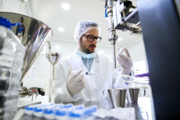 Chemist checking water quality while holding syringe and bottle in his hands. Protective suit and gloves on, lab interior.