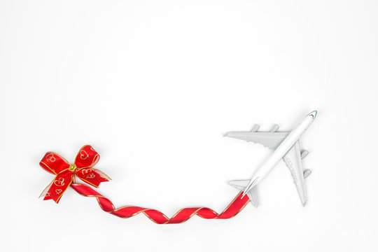 Travel holiday concept. White model of passenger plane with heart bows over white background, top view. Special for travel holiday on New years or Valentines.