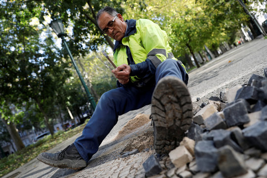 Paver Jorge Duarte works on the repair of Portuguese pavement in Lisbon