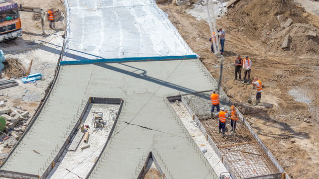 Concrete works for road construction with many workers and concrete pump timelapse