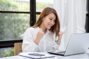 Beautiful Attractive Asian woman celebrating with laptop after success job feeling so happy and cheerful,Business Startup concept