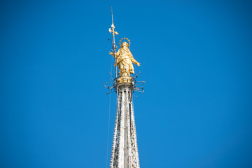 Aluminium Prints Historic monument Golden Virgin Mary statue on top roof of Duomo cathedral in Milan, Italy
