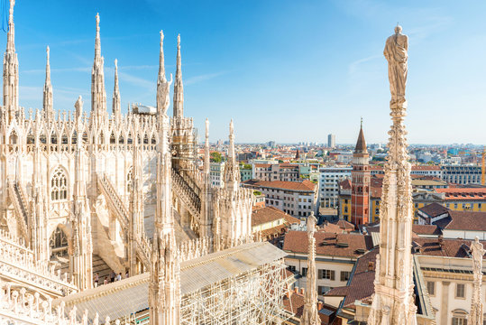 White statue on top of Duomo cathedral and view to city of Milan