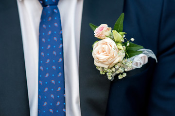 detail of a groom's dark blue costume with a buttonhole of roses - selective focus, space for text