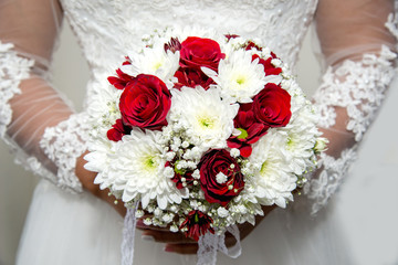 Beautiful bride in a wedding dress holding a bouquet of red tulips. White background. Text space.