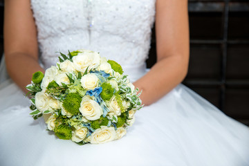 Beautiful bride in a wedding dress holding a bouquet of yellow roses. White background. Text space.