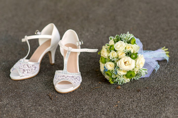 bridal bouquet and lace shoes on gray stone - close-up