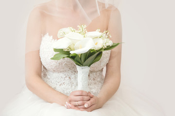 Beautiful bride in a wedding dress holding a bouquet of white zantedeschia. White background. Text space.