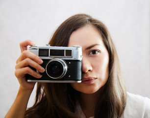 A young woman photographs with an analog camera