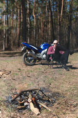man near campfire enjoying summer day in forest. off road motorcycle, enduro bike, biker resting outdoors, vertical photo