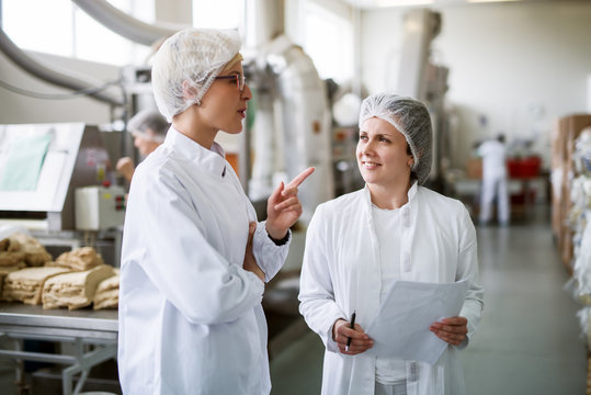 Two female workers discussing while standing in food factory.