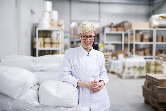 Smiling Caucasian female worker leaning on bags with flour in warehouse. Woman looking at camera. Protective suit on.