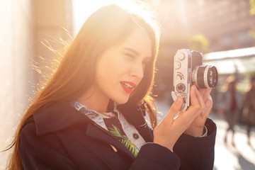 Outdoor autumn smiling lifestyle portrait of pretty young woman, having fun in the city with camera, travel photo of photographer.