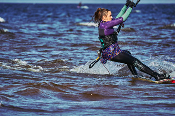 A female kiter slides on the surface of the water. Splashes of water fly apart. Close-up.