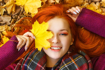 Portrait of a beautiful red-haired girl with fallen autumn maple leaves. (People Beauty/Fashion)