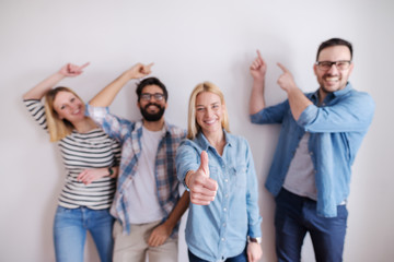Small group of people pointing on the wall and one girl gives thumbs up. Start up business concept.