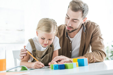 father looking at cute little daughter writing in workbook and learning at home