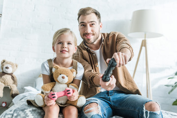 happy father and cute little daughter with teddy bear playing with joysticks at home