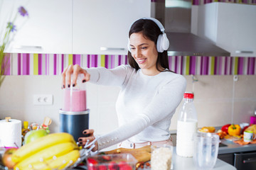 Cute young girl in kitchen mixing her favorite fruits for breakfast. Holding headsets on her head.