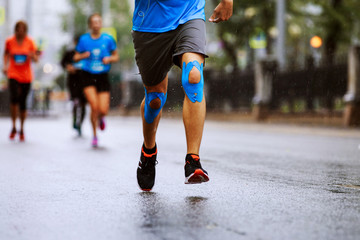 Fototapete - legs male runner kinesio tape on knees running marathon in rain